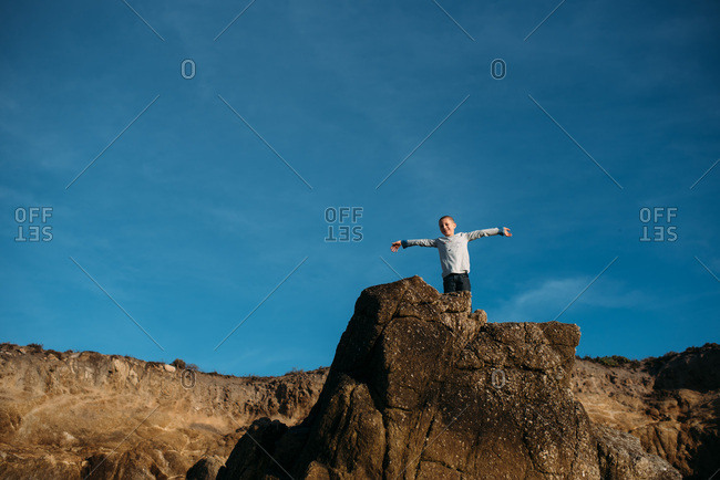Boy standing at the top of a rock formation with arms held out
