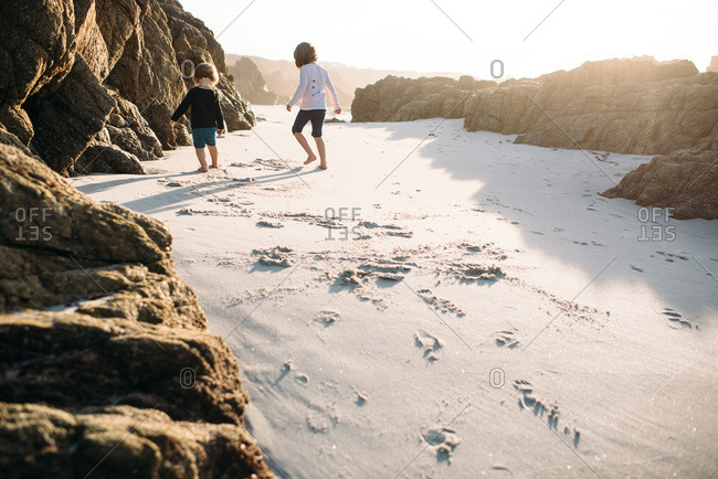 Two girls walking in sand on the beach near some rocks