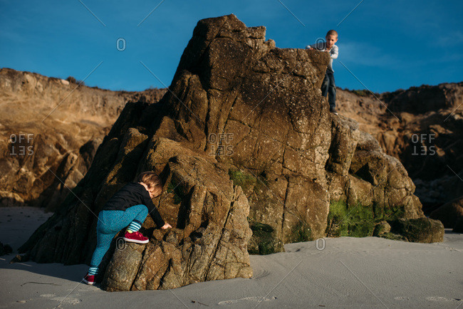 Kids climbing on rocks at the beach in Pebble Beach, California