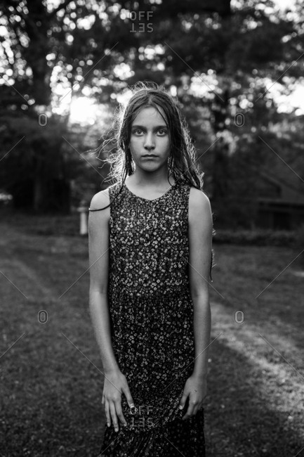 Pre-teen standing outside in black and white