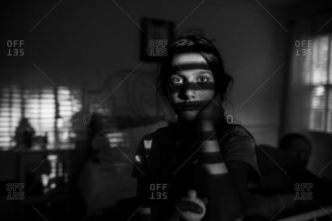 Pre-teen stars at window blinds alone in dark