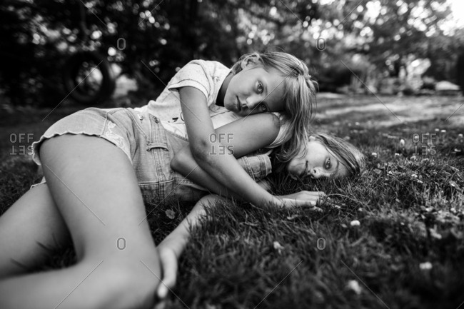 Young girls lying in grass together in black and white