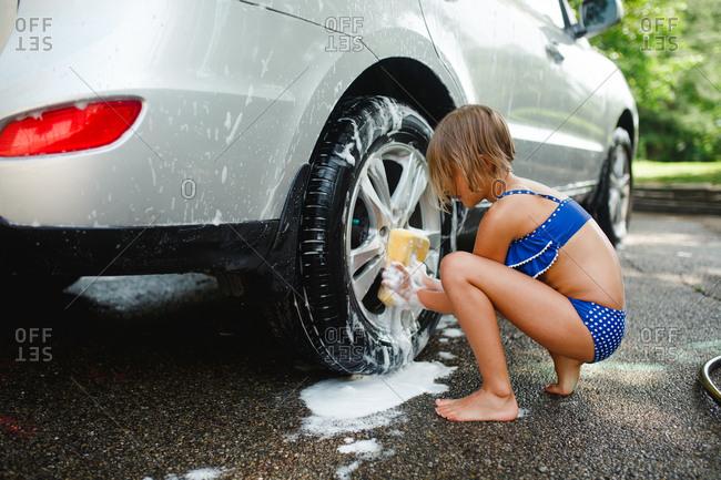 Girl washing car in bathing suit