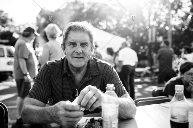 Man eating at table outside in black and white