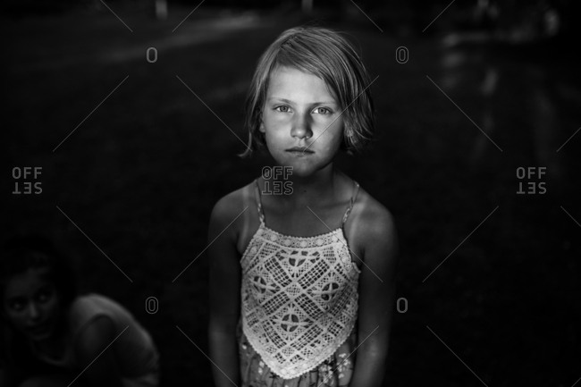 Serious child standing outside in black and white