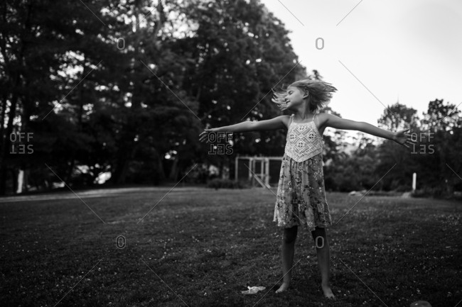 Playful child stretches arms outside in black and white