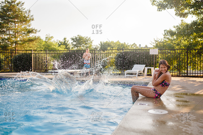 Young girl hides her face as someone cannon balls into a pool