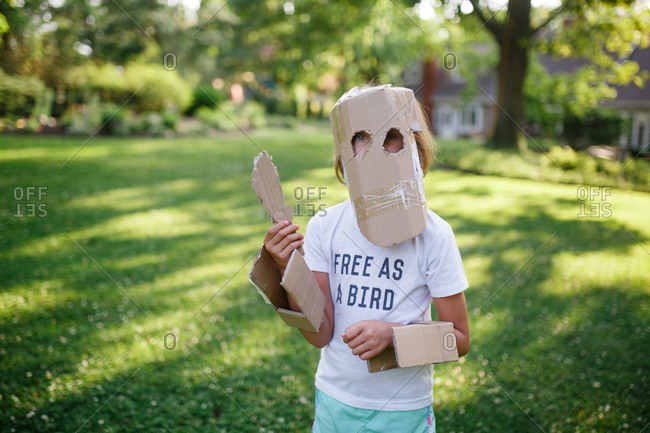 Young child poses wearing home made cardboard armor