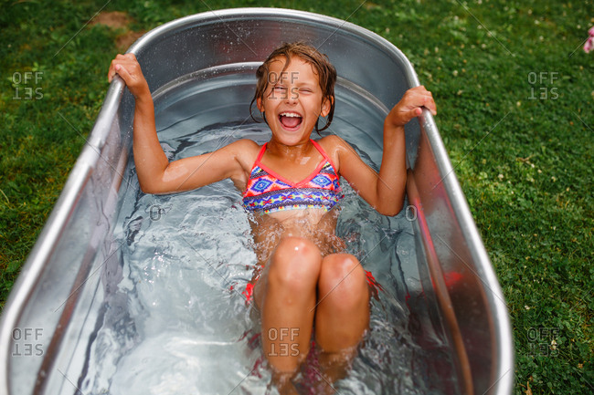 Young girl laughs as she gets into a metal tub of water