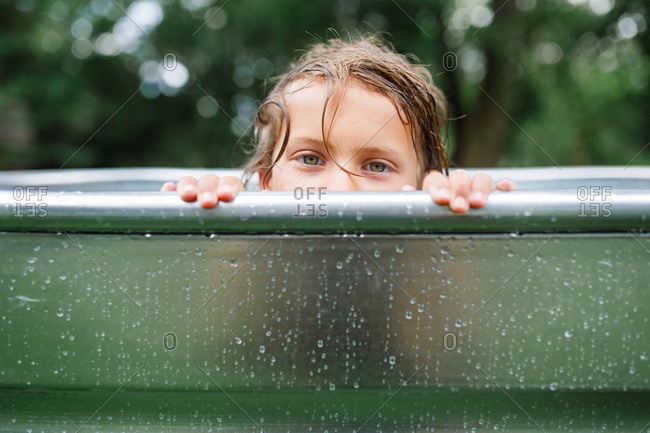 Young child peers over the edge of a swimming pool