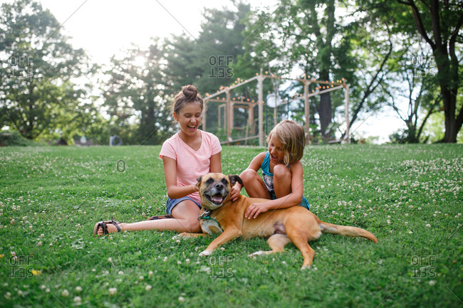 Two young girls play with their dog in their backyard