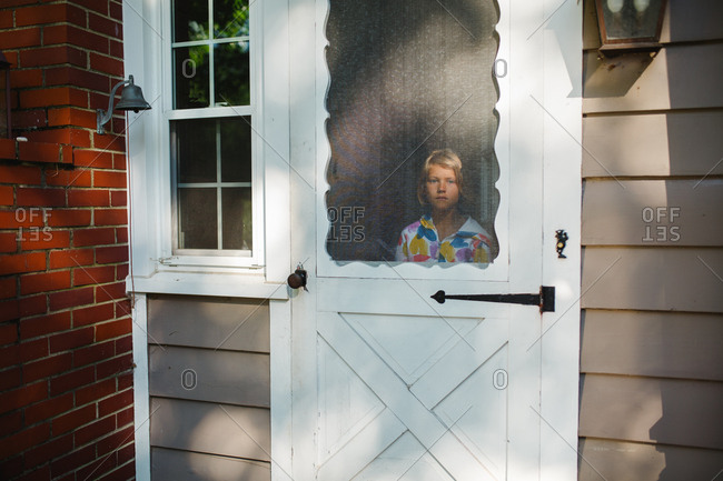 Young girl looks out through a screen door of a rustic house
