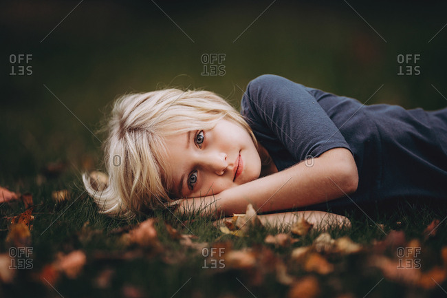 Girl lying on grass and leaves