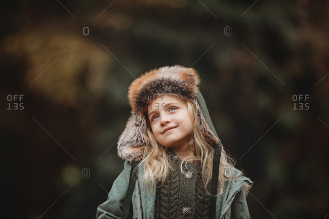 Girl with hooded jacket smiling off camera