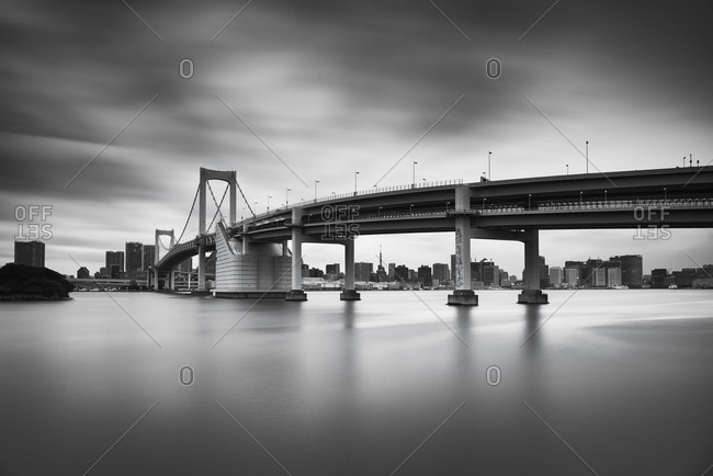 Black and white long exposure of the sunset sky over Rainbow bridge in Odaiba, Tokyo, Japan