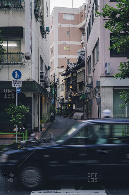 Tokyo, Japan - October 12, 2017: Taxi passing in front of narrow alley with traditional building downtown Tokyo, Japan