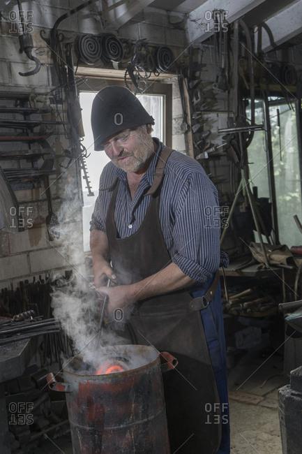 Blacksmith cooling down hot iron bar at workshop