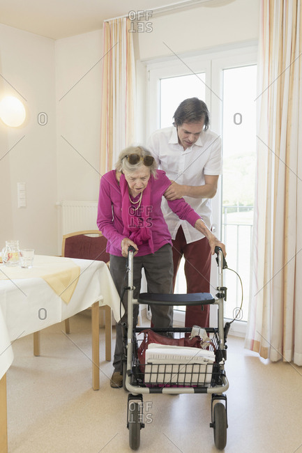 Caretaker helping senior woman using wheeled walker