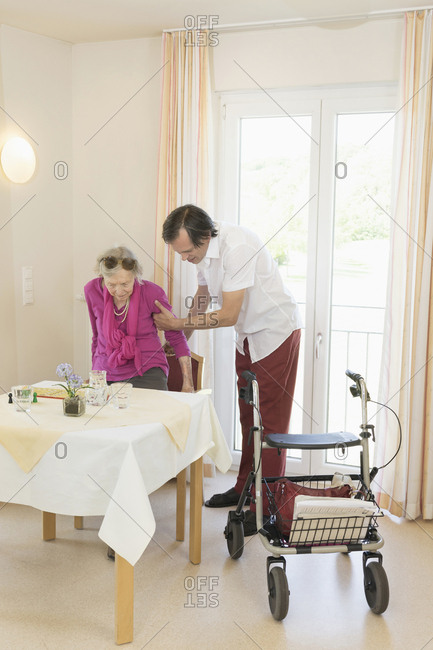 Caregiver helping senior woman using wheeled walker