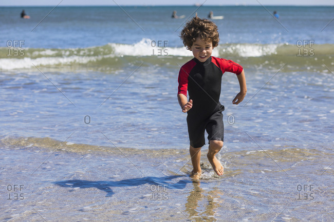 Little boy running out of the sea