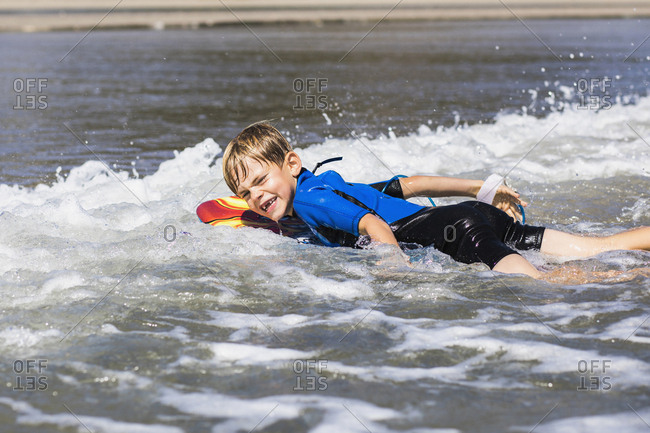 Portrait of boy surfboarding on sea