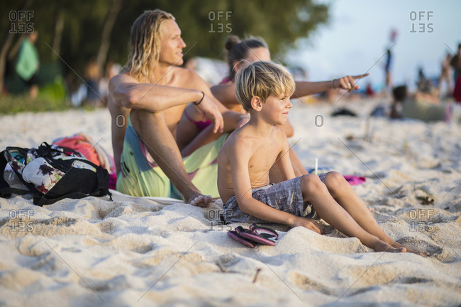 Family relaxing on sand at beach