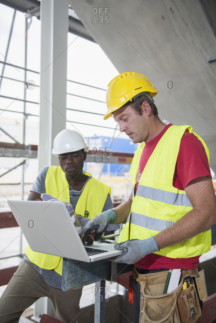 Construction workers working on laptop at building site
