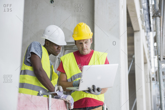 Construction workers using laptop at site