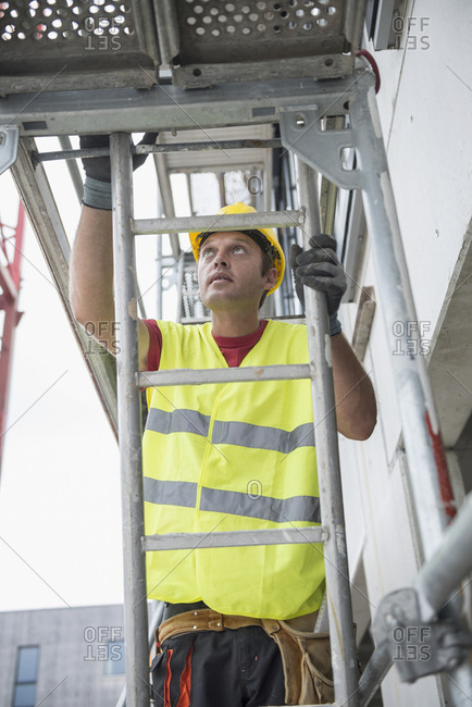 Construction worker at building site climbing up a ladder