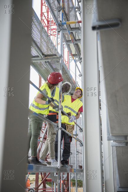 Construction workers verifying the building site on scaffold