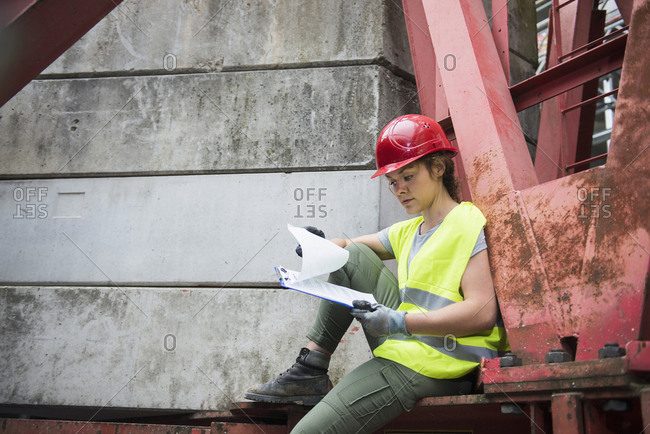 Female construction worker with architectural plan at building site