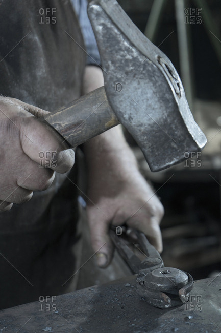 Blacksmith hammering iron on anvil at workshop
