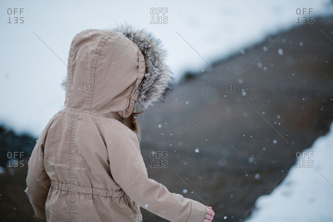 Child wearing a hooded jacket on a snowy day