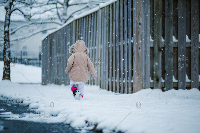 Child walking through snow covered neighborhood