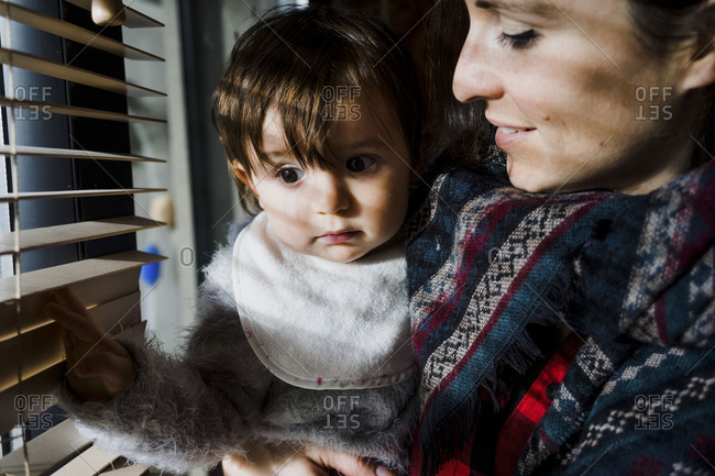 Mother holding toddler looking out window