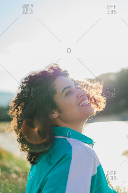 Portrait of young ethnic woman with curls laughing and looking up on background of sunlight and nature.