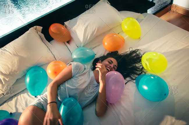 Girl having fun at night in her room taking photos and playing with balloons