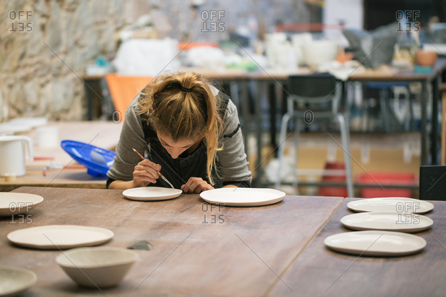 Woman creating clay plates in workshop