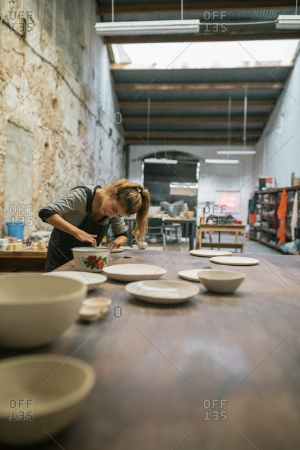 Concentrated woman in overall sitting at table and creating plates from white clay.