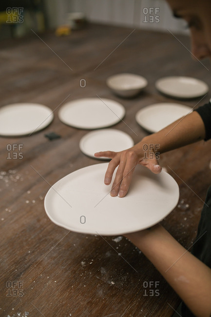 Crop person working with ceramic plate