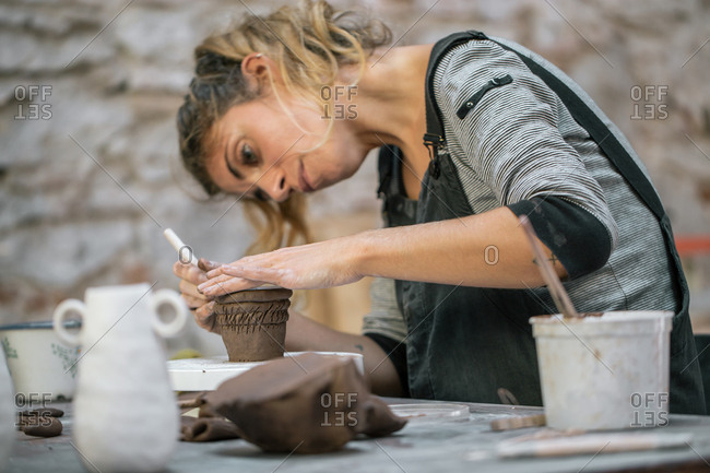 Crop woman working with clay