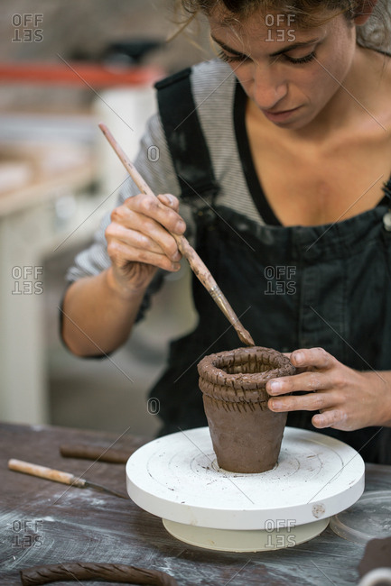 Woman working with clay making pot
