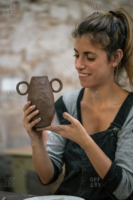 Serious woman shaping pot from clay