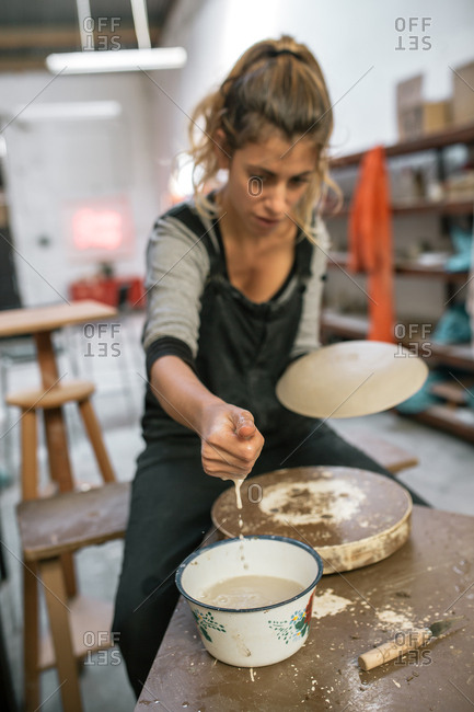 Woman moistening piece of clay