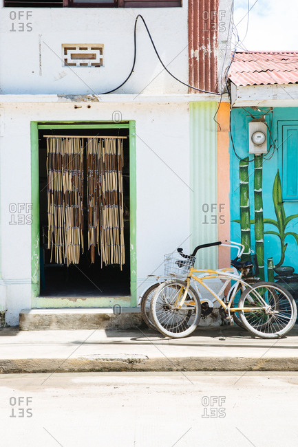 San Juan Del Sur, Nicaragua - May 11, 2017: Bicycles leant up against a wall outside an open doorway