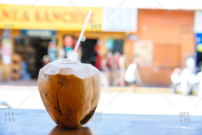 Coconut ready to drink on a table in a street side cafe