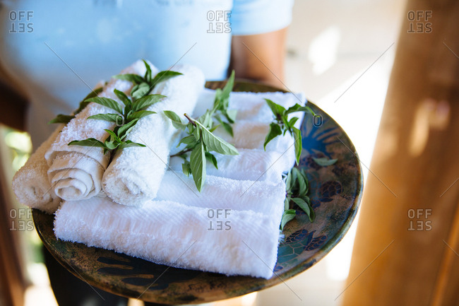 Spa worker offers rolls of fresh towels