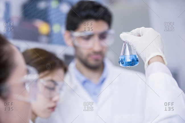 Lab assistants looking at flask