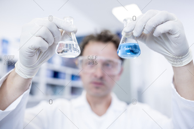 Lab assistant holding two chemical flasks