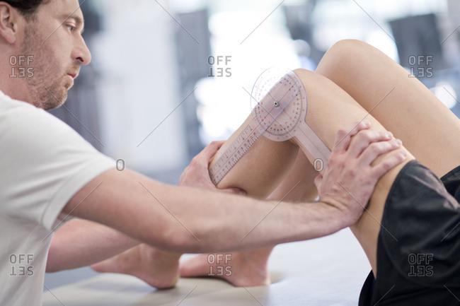 Physiotherapist measuring woman's leg